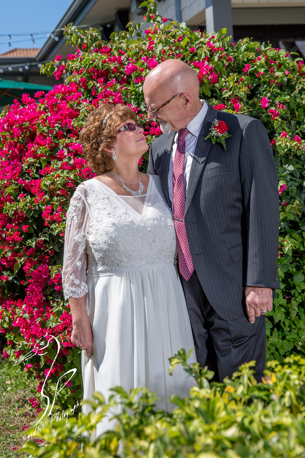 Anna Maria Oyster Bar Wedding Photography Bride Groom outside pink flowers outside sunny