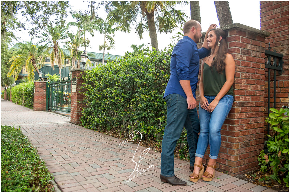 Downtown Bradenton Engagement Photography an engaged woman leans against a pillar as her fiance leans in towards her intimately