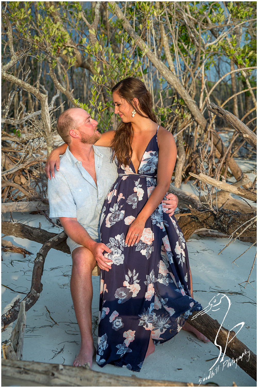 Beer Can Island Engagement Photography, engaged couple sitting on drift wood in front of the mangroves on the beach and smiling at each other