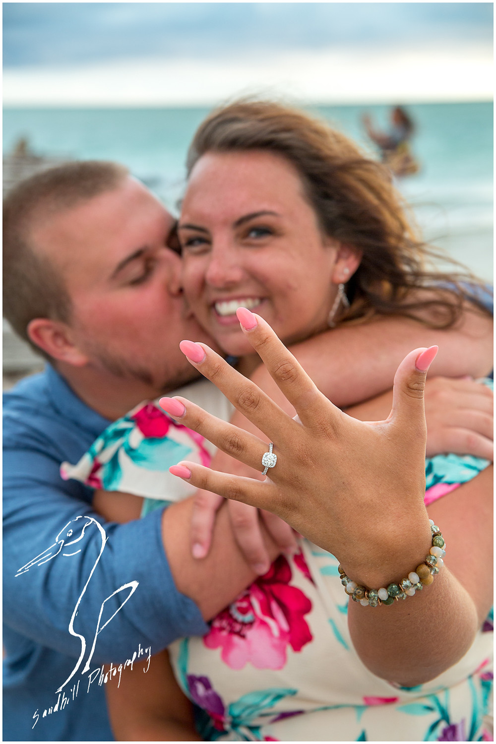 Bradenton Beach Engagement Photography Couple kissing in background while she holds out her hand to show her Engagement Ring
