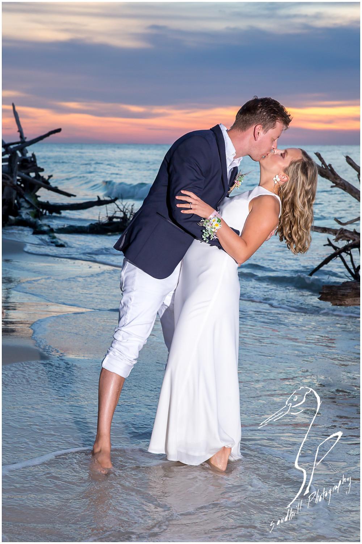 Anna Maria Island Wedding Photography, couple kiss for sunset beach wedding portrait, by Sandhill Photography