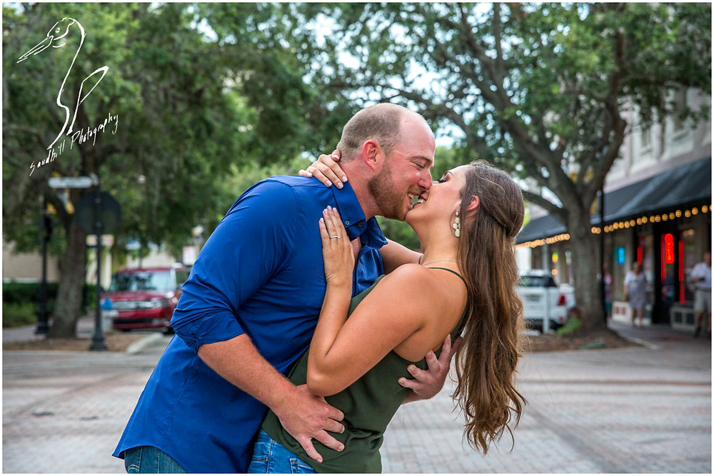 Downtown Bradenton Engagement Photography, in the middle of Old Main St., an engaged couple lean back, laughing just before sharing a kiss