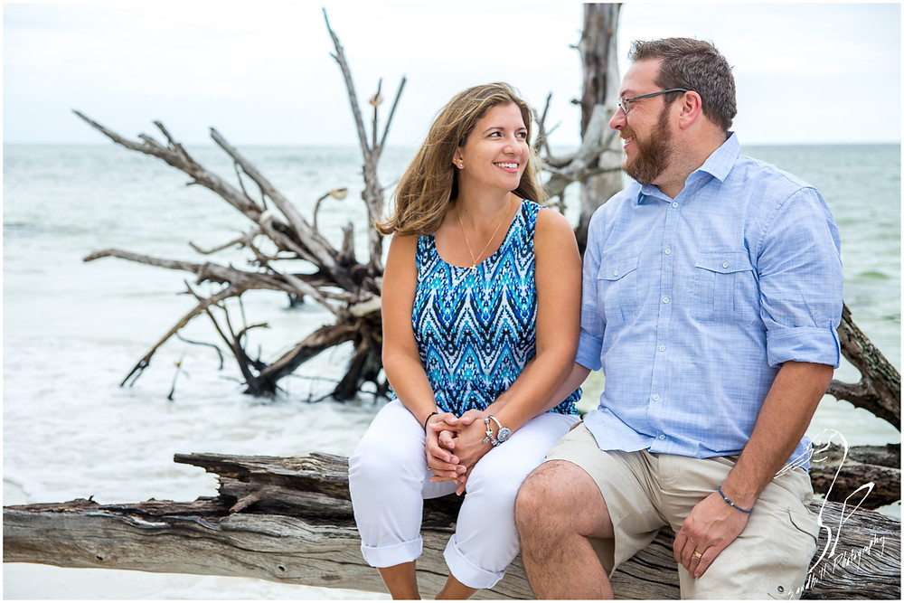 Longboat Key Family Photographer, mom and dad smile at each other in front of driftwood in the ocean at Beer Can Island
