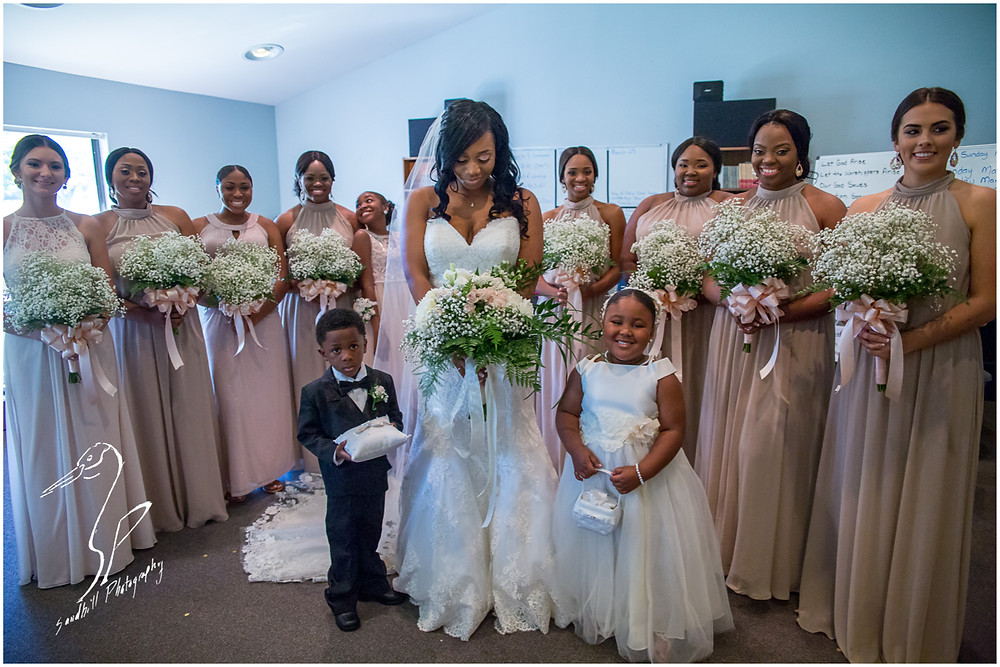 Bradenton Wedding Photographer, the bride casts her eyes towards her bouquet while surrounded by her bridal party at United First Methodist Church of Seffner