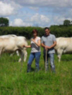 Catherine et Christian Gauthey au milieu de leurs vaches dans un pré