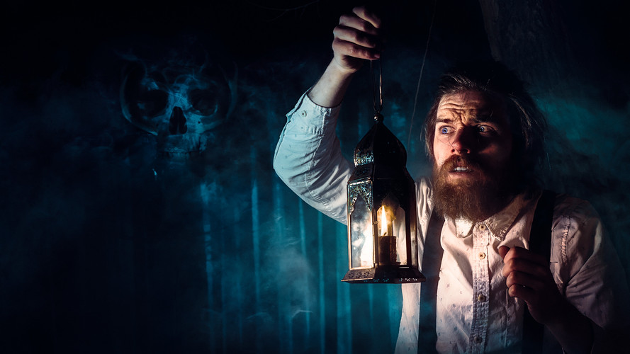 Terrfied man stands in a dark creepy forest holding a lantern a evil skull can be seen in the fog in this supernatural photo by Photographer Dillon Vance