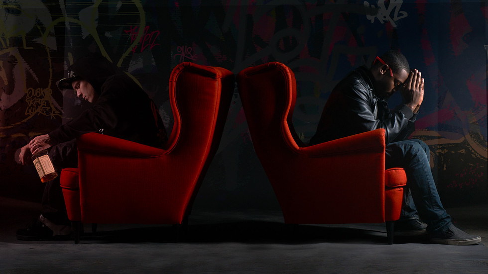 Two Men sit back to back in red chairs on praying and the other with alcohol opposing each other in this conceptual photo
