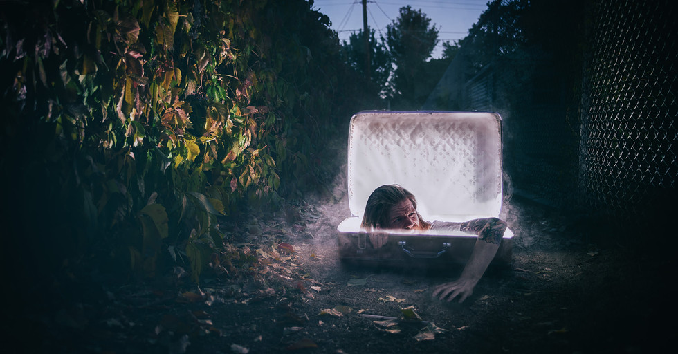 A Magical Suitcase sits open and glowing on a dirt walk way in Reno, NV a person crawls out of a portal in the suitcase in this surreal photograph by Dillon Vance