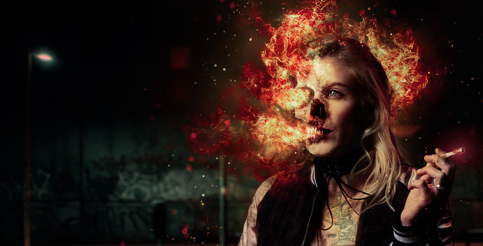 A Moody Cosplay Photo Manipulation of a tattooed woman smoking a cigarette with a flaming skull for a head like a Super Villian by photographer Dillon Vance of Reno, NV