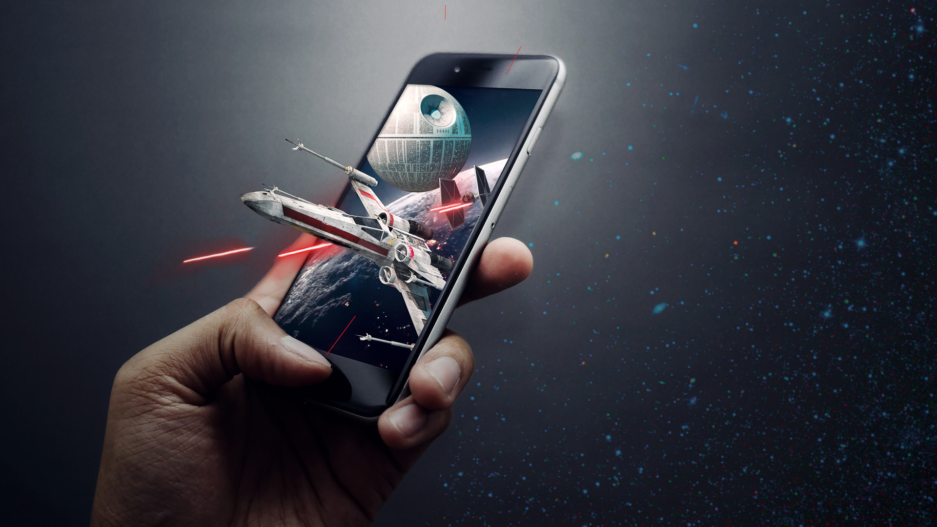 A hand holding a phone as star wars spaceships burst from the screen in this advertising photo inspired by Lucas Arts and created by Dillon Vance Photo