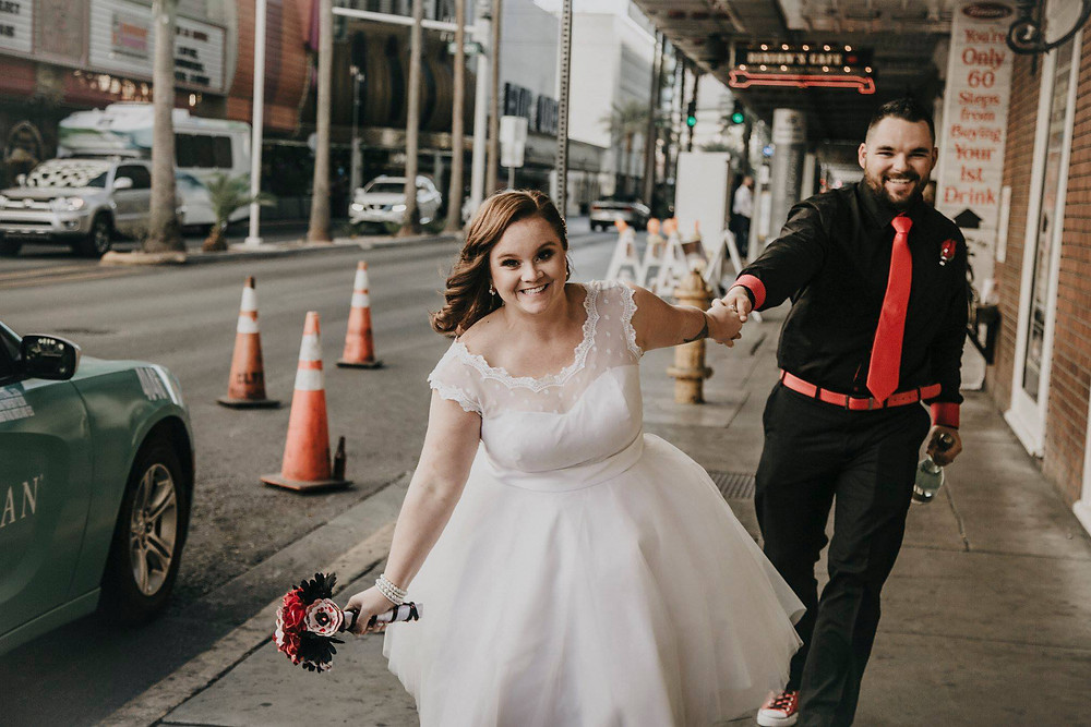 Bride and groom run through the streets of Las Vegas during their downtown city elopement.