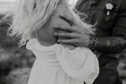 Grooms hand with tattoos Rubs his bride's shoulders.