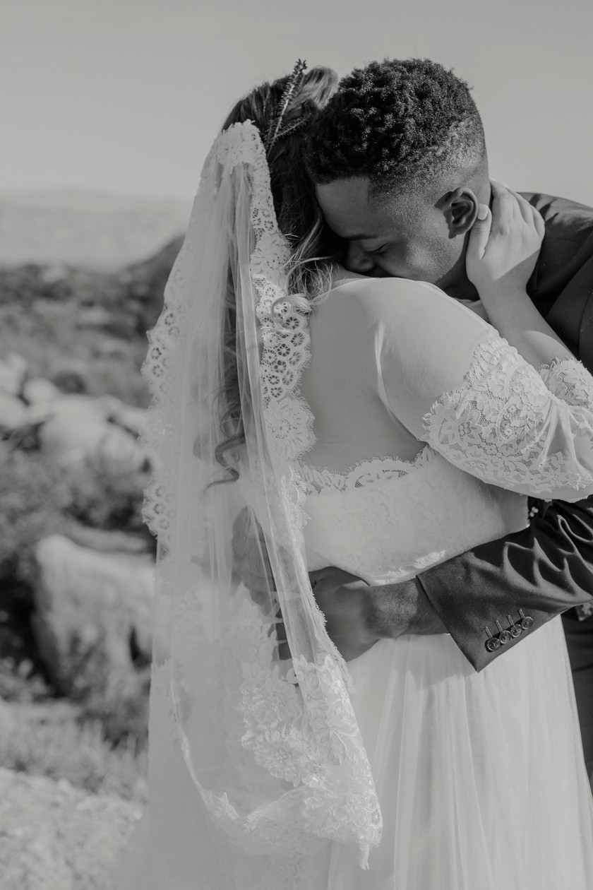 He holds her tight Atop a beautiful mountain with views of the city moments before they say their vows.