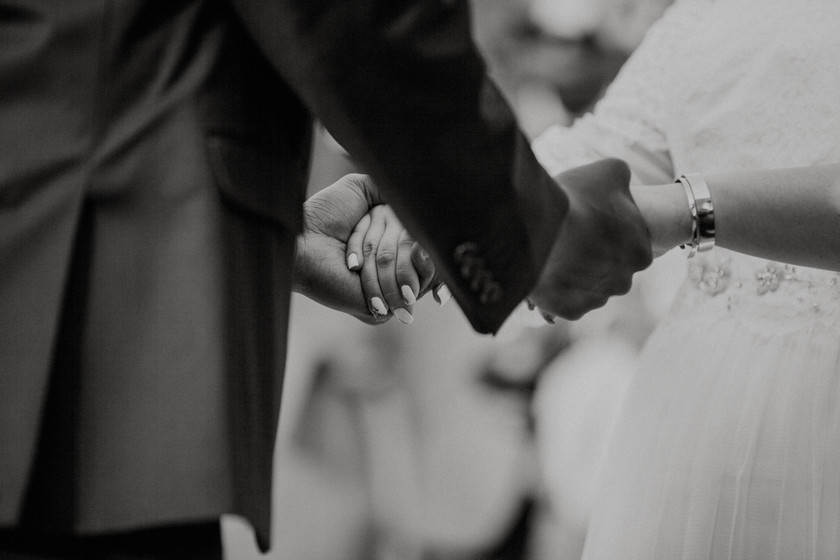 bride and groom hold hands During a small and intimate ceremony in the woods.