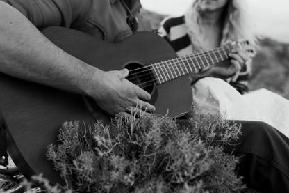 Tattooed hand plays guitar in the desert.