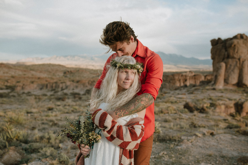 Couple says vows In Desert canyon as clouds rolled in.