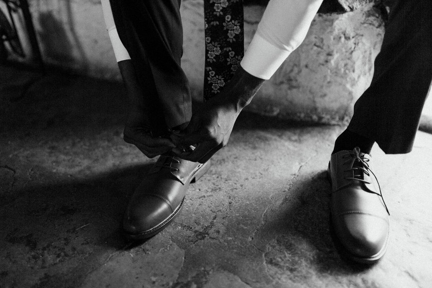 Groom tying his shoes in a mountain cottage while his bride awaits.