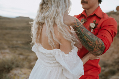 Groom relaxes bride During an intimate wedding ceremony.
