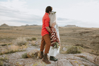 Couple overlooks canyon During an elopement ceremony in a desert canyon.