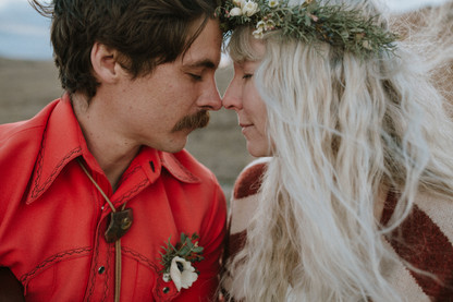 Couple sits nose to nose During an elopement ceremony.
