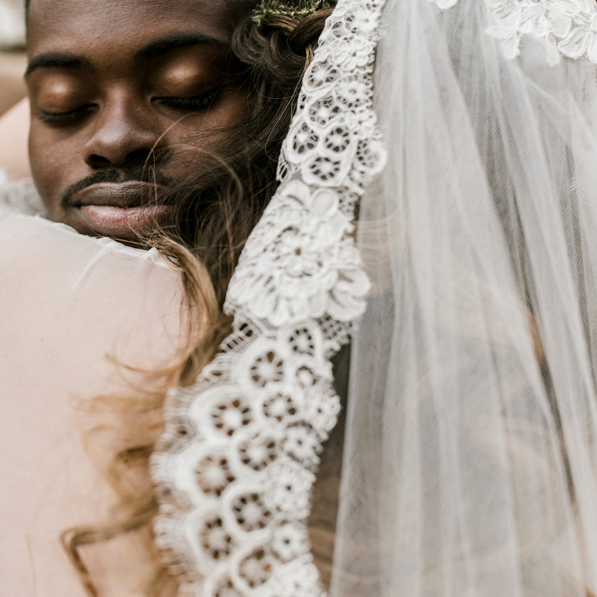 close up of grooms face as he hugs his beautiful bride during the ceremony