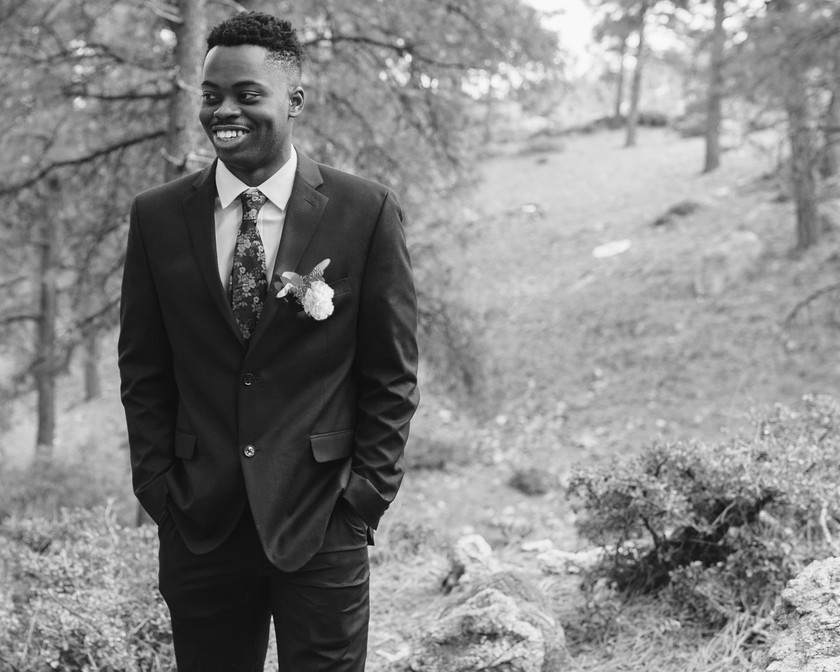 Portrait of a groom, in a tuxedo with a boutonniere.
