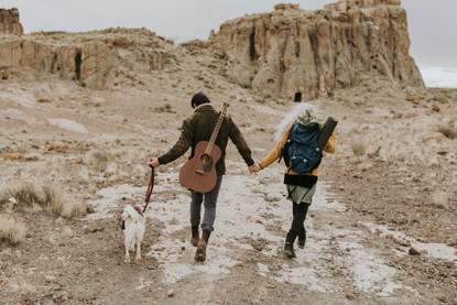 A couple elopes With a guitar and a backpack with a bouquet along with their dog to a beautiful canyon Arizona.