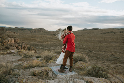 Couple dances on rug On top of a mountain in the desert.