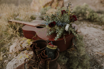 Shot of guitar and bouquet create the perfect details for a bohemian couple.