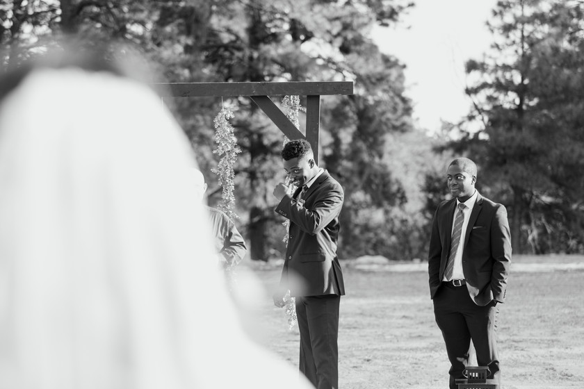 The groom cries As his bride walks towards him during a small mountain elopement ceremony.
