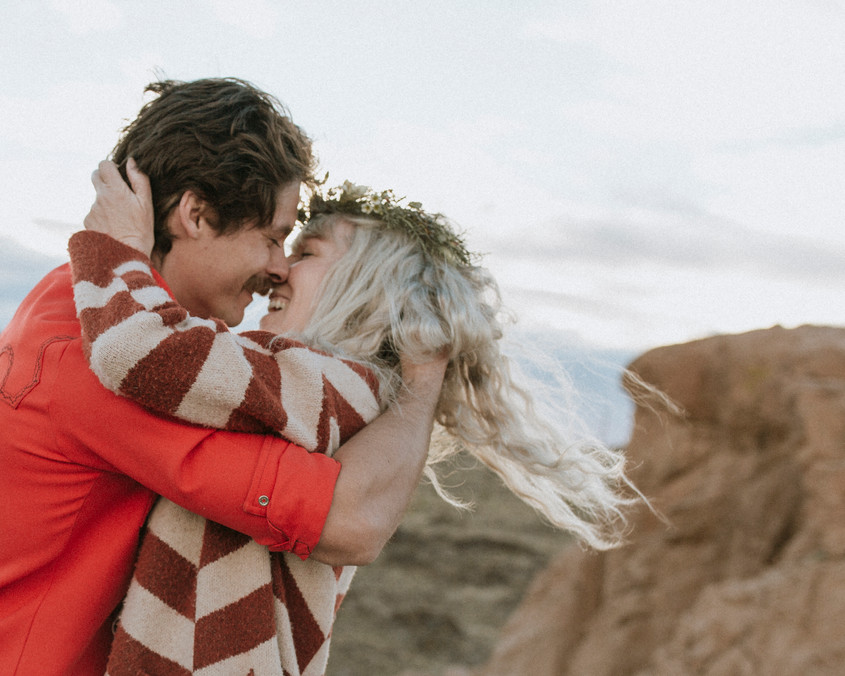 Bride and groom kiss As the wind blows her hair atop a desert canyon.