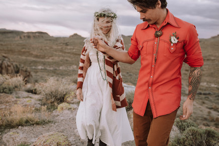 Bride and groom hold hands As he leads her in desert.