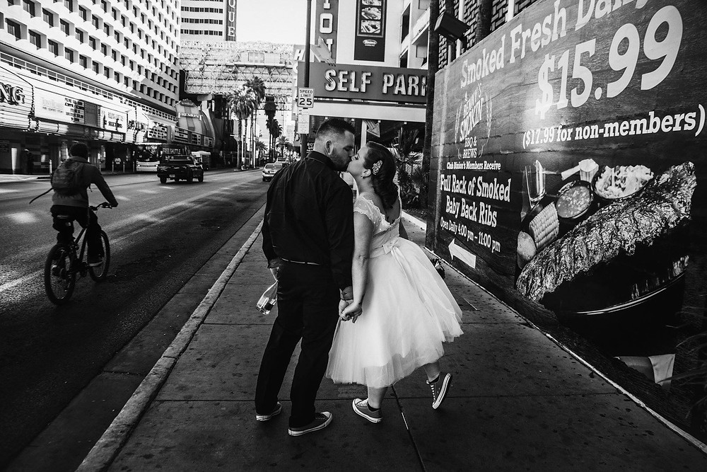 Downtown urban elopement, bride and groom kiss on the streets of Las Vegas.