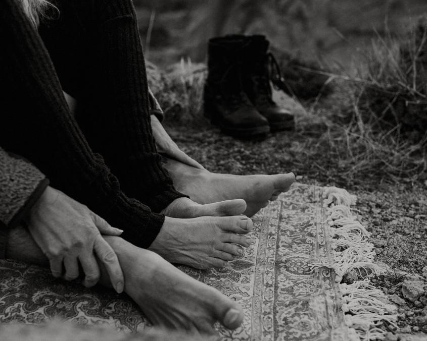Bare feet on bohemian rug with some yoga and beautiful desert rocks.