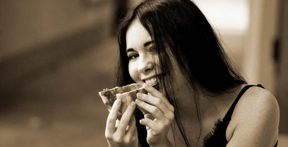Junge Frau isst Pizza mit Händen in Strassen von Ascona