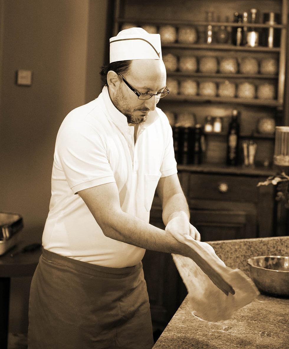 Sergio der Pizzaiolo formt Teig in Küche