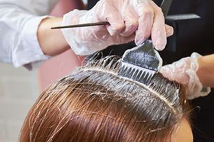 Hair dying close up. Brush applying hair