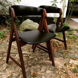 To smukke Henning Kjærnulf stole i teak med sort skai på sæde og ryg. Flot stand med naturlige brugs