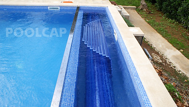Poolabdeckung Rolloabdeckung Polycarbonat 15/60 mm kristallblau-transparent. Welle in einer Beckenverlängerung oben, Holzabdeckung abgenommen.