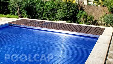 Poolabdeckung Rolloabdeckung Polycarbonat 15/60 mm kristallblau-transparent. Welle in einer Beckenverlängerung oben, abgedeckt mit Holzelementen