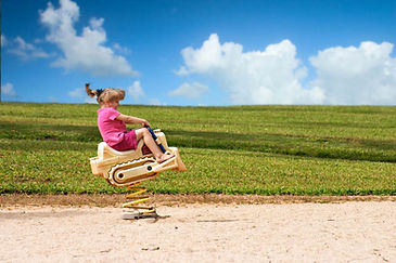 Little girl with flying pigtail on bouncy tractor at playground