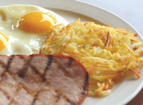 A breakfast plate featuring crisp hash browns, a sunny-side-up fried egg, and a slice of ham.