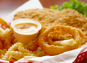 A basket of crispy onion rings and fries, with a small cup of dipping sauce.