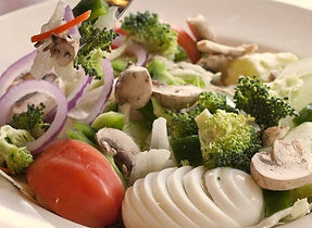 A fresh salad, featuring sliced boiled egg, tomato, broccoli, mushroom, and red onion.