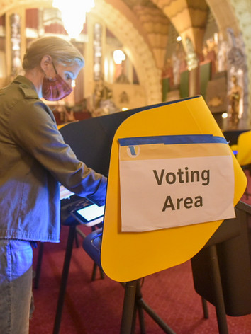 Poll workers wipe down each station after every use at the Pantages Theatre voting center in Los Angeles for the 2020 General Election.