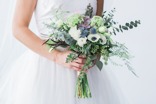 bride with wild green and white bouquet