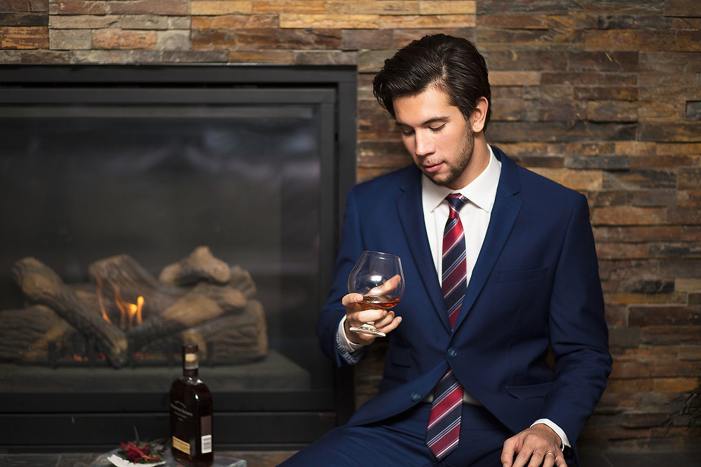 Groom drinking bourbon by the fire