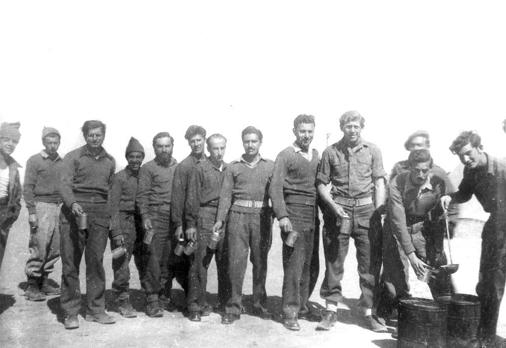 בשבי- ראובן מילון (מימין) מחלק אוכל לחבריו במחנה השבויים באום אל ג'מאל, באדיבות ראובן מילון