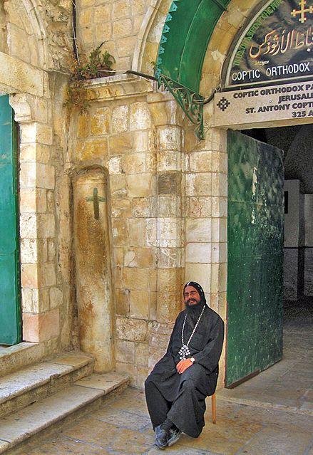 נזיר קופטי ליד העמוד המעוטר בצלב