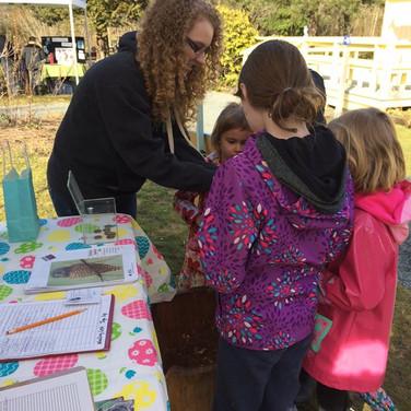Volunteer Alyssa playing the Nest Stump game with kids